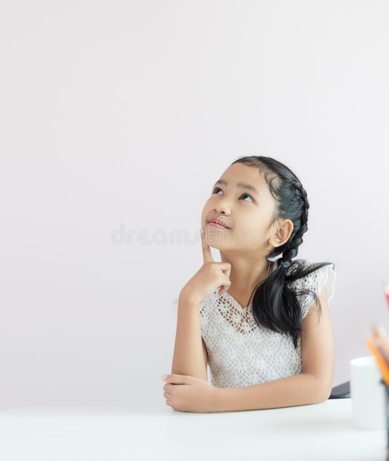 Portret małej Azjatyckiej dziewczyny siedzący główkowanie coś i uśmiech z szczęście wybiórki ostrości płytką głębią pole z kopii  fotografia royalty free