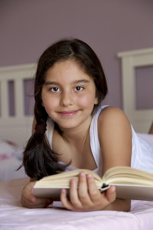 Portret małej dziewczynki czytanie w łóżkowym pokoju zdjęcia royalty free