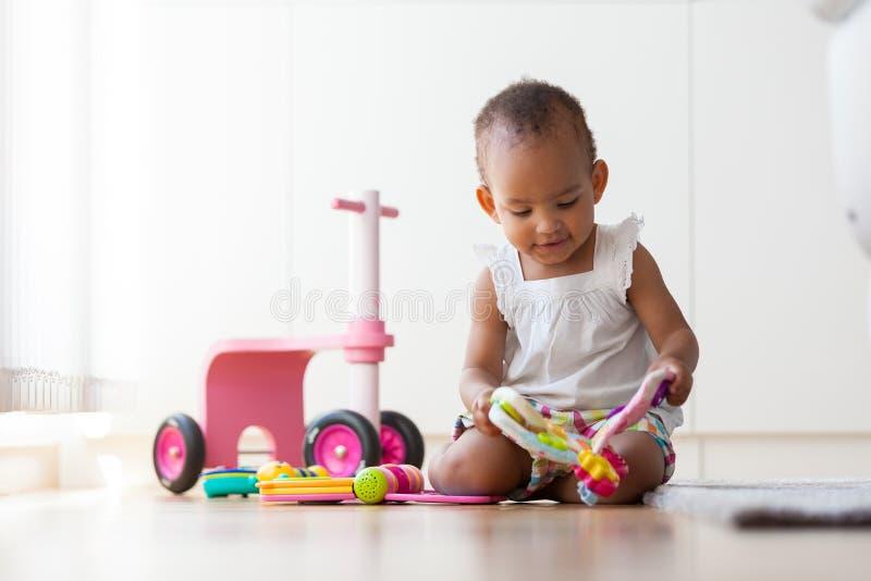 Portret mały amerykanin afrykańskiego pochodzenia małej dziewczynki obsiadanie na f zdjęcie stock