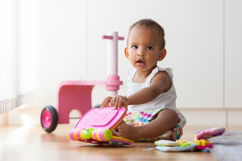 Portret mały amerykanin afrykańskiego pochodzenia małej dziewczynki obsiadanie na f zdjęcia royalty free
