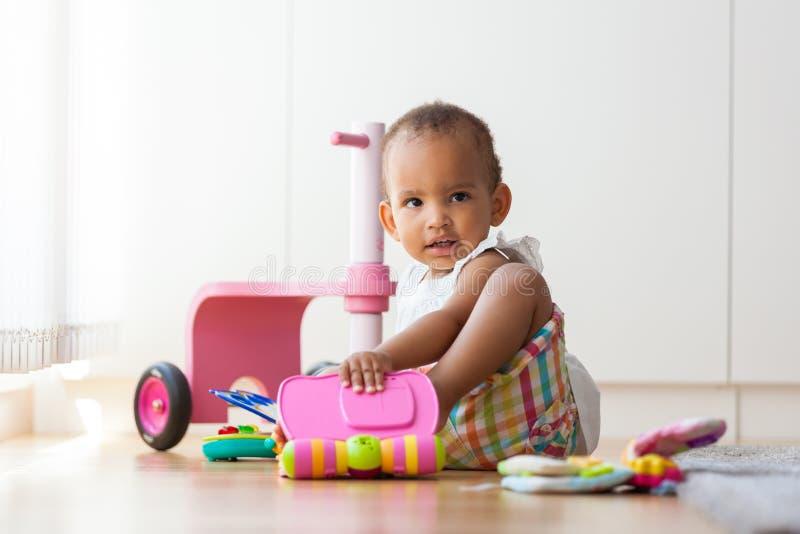 Portret mały amerykanin afrykańskiego pochodzenia małej dziewczynki obsiadanie na f obraz stock