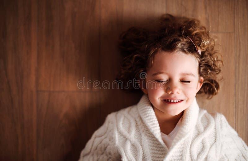 Portret ma?a dziewczyna z bia?ym trykotowym puloweru lying on the beach na pod?odze, odg?rny widok obraz royalty free