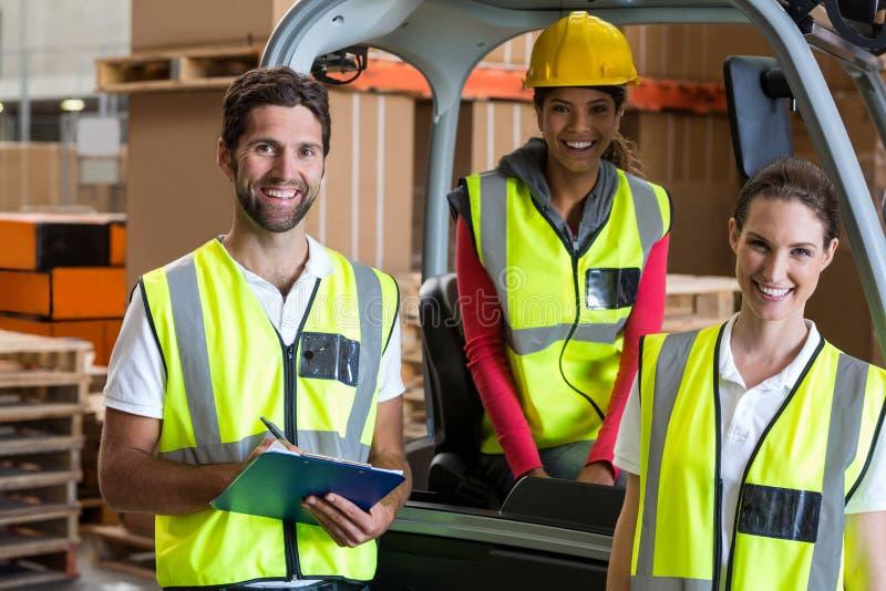 Portret magazynowi pracownicy i forklift kierowca obraz stock