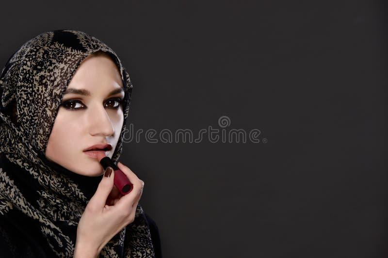 Portret maluje jej wargi z pomadką Muzułmańska kobieta obraz stock