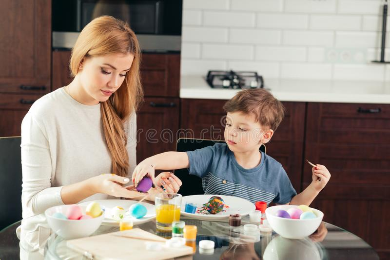Portret maluje Wielkanocnych jajka z jej uroczym małym synem szczęśliwa młoda kobieta fotografia royalty free