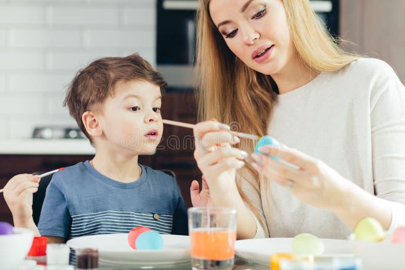 Portret maluje Wielkanocnych jajka z jej uroczym małym synem szczęśliwa młoda kobieta obraz royalty free