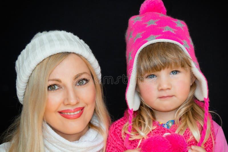 Portret Mama i córka, w trykotowych kapeluszach na czarnym tle, Szczęśliwa rodzina, uśmiechy i radość, fotografia stock
