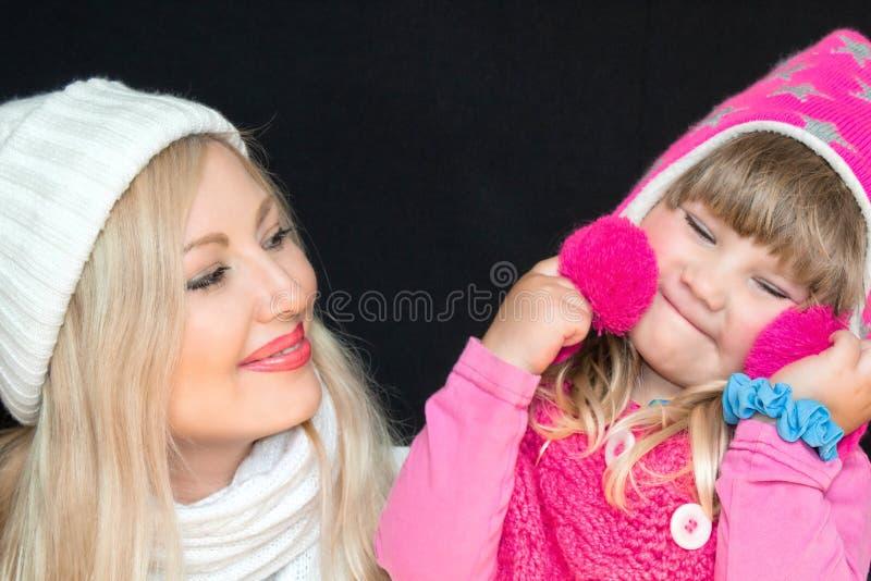 Portret Mama i córka, w trykotowych kapeluszach na czarnym tle, Szczęśliwa rodzina, uśmiechy i radość, zdjęcia royalty free