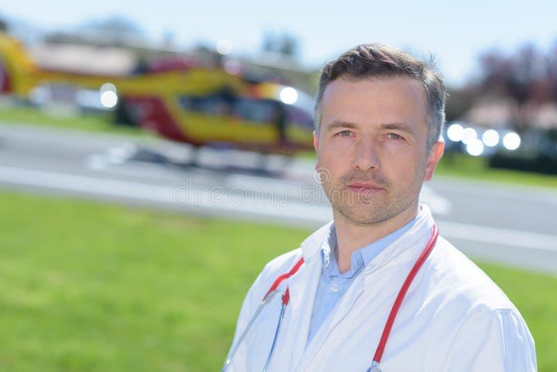 Portret mannelijke arts dichtbij noodsituatiehelikopter royalty-vrije stock afbeelding