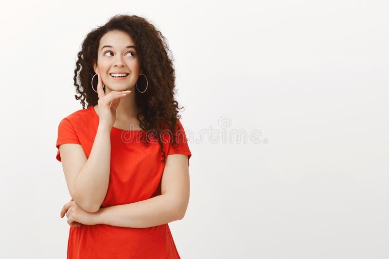 Portret marzycielska atrakcyjna elegancka dziewczyna z kędzierzawym włosy w czerwieni sukni, ono uśmiecha się joyfully podczas gd fotografia royalty free