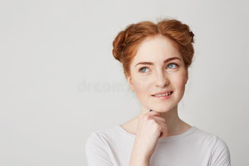 Portret marzycielski młody ładny imbirowy dziewczyny główkowanie marzy wzruszającego podbródka uśmiechniętą zjadliwą wargę nad bi zdjęcie stock