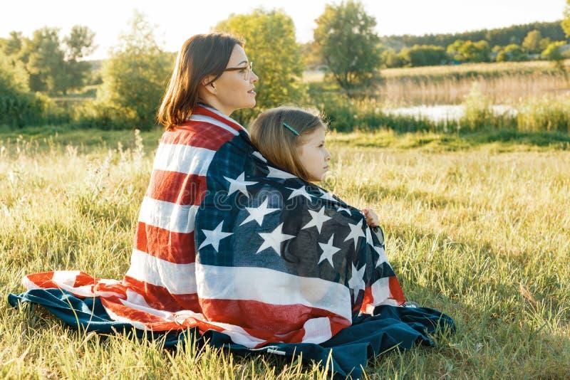 Portret matki i dziecka córka z flagą amerykańską Patrzeć naturalnego wiejskiego krajobraz, widok od plecy obraz stock