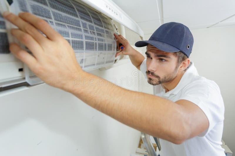 Portret medio-volwassen mannelijke technicus die airconditioner herstellen royalty-vrije stock afbeeldingen