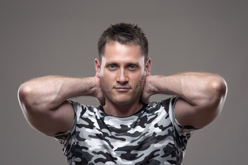 Portret mięśniowy sportowy młody dorosły mężczyzna w wojsko koszula pozuje z rękami za głową obrazy royalty free