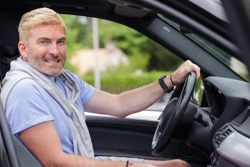 Portret midden oude mannelijke bestuurder achter wiel stock afbeelding
