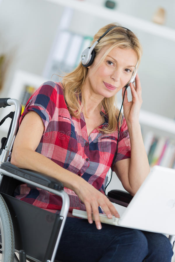 Portret midden oude vrouw in rolstoel met laptop en hoofdtelefoons stock afbeeldingen