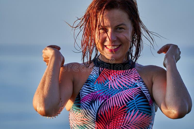 Portret miedzianowłosa mokra roześmiana kobieta wiek średni w swimsuit na lato wieczór w świetle położenia słońca obraz stock