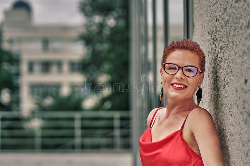 Portret miedzianowłosa roześmiana w średnim wieku kobieta w czerwonej bluzki pozycji przeciw ścianie Chmurny letni dzie? zdjęcie stock