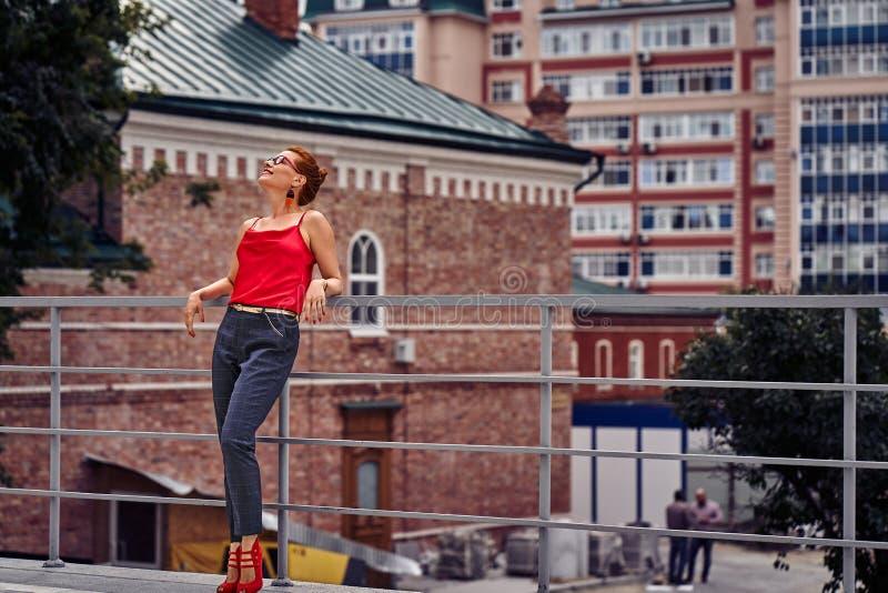 Portret miedzianowłosa w średnim wieku kobieta w czerwonej bluzce w szkłach i podczas gdy chodzący wokoło miasta Chmurny letni dz zdjęcia royalty free
