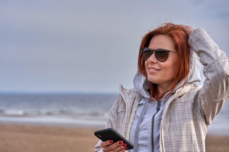 Portret miedzianowłosa w średnim wieku kobieta patrzeje smartphone w okularach przeciwsłonecznych i deszczowiec pogodna ranek wio fotografia royalty free