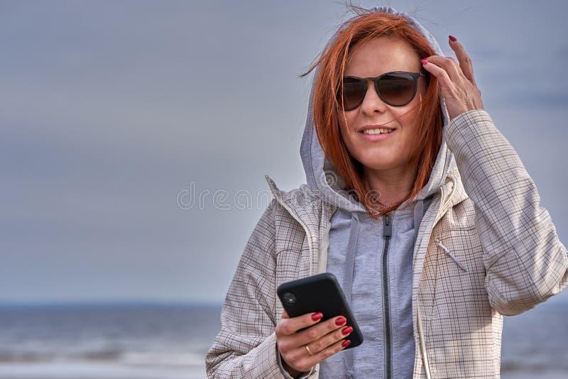 Portret miedzianowłosa w średnim wieku kobieta trzyma smartphone w jej ręce w okularach przeciwsłonecznych i deszczowiec pogodna  zdjęcia stock