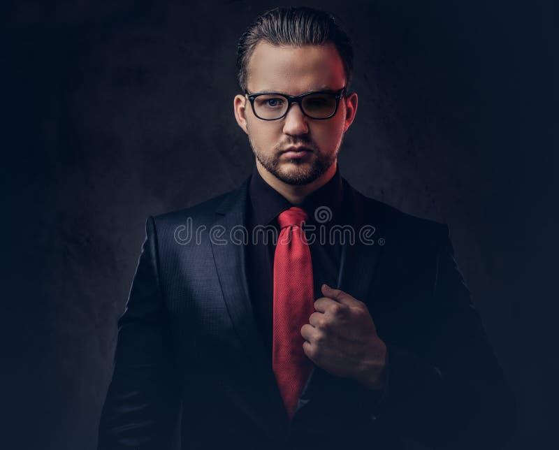 Portret mistyczna elegancka samiec w czarnym kostiumu czerwonym krawacie i Odizolowywający na ciemnym tle zdjęcia royalty free
