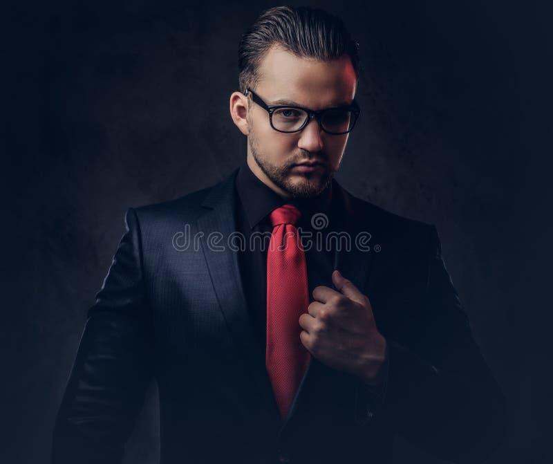 Portret mistyczna elegancka samiec w czarnym kostiumu czerwonym krawacie i Odizolowywający na ciemnym tle fotografia royalty free