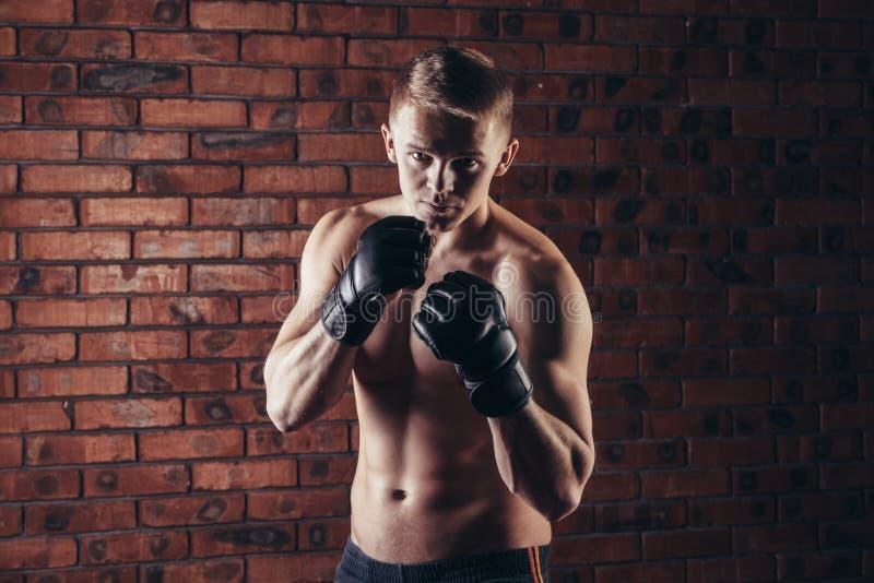 Portret mma wojownik w boks pozie przeciw ściana z cegieł obraz stock