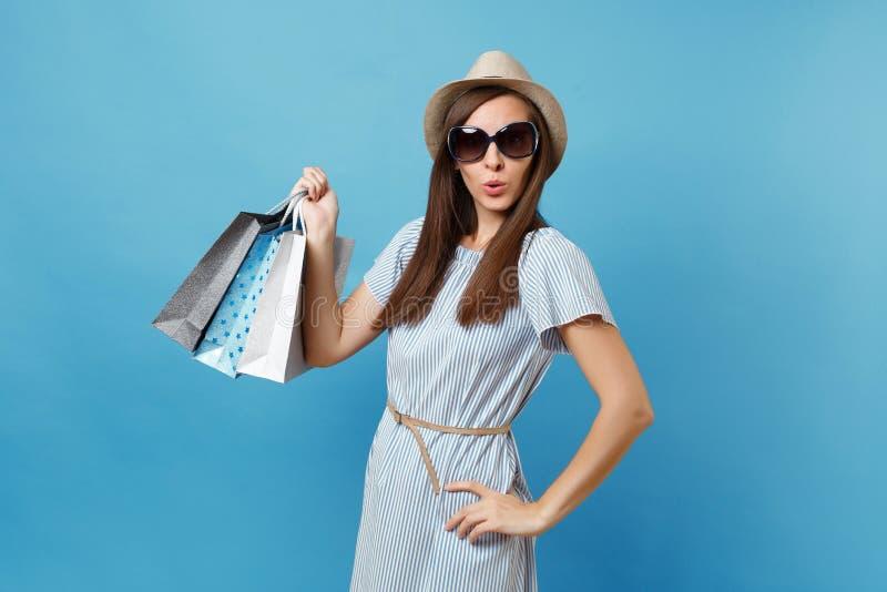 Portret modieuze aantrekkelijke gelukkige vrouw die in de zomerkleding, strohoed, zonnebril pakkettenzakken met aankopen houden royalty-vrije stock foto's