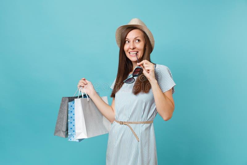 Portret modieuze aantrekkelijke gelukkige vrouw die in de zomerkleding, strohoed, zonnebril pakkettenzakken met aankopen houden royalty-vrije stock fotografie