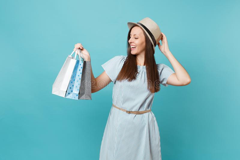 Portret modieuze glimlachende mooie Kaukasische vrouw in de zomerkleding, de zakken van de holdingspakketten van de strohoed met  stock foto