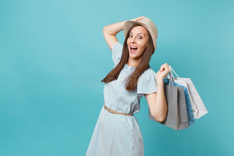 Portret modieuze glimlachende mooie Kaukasische vrouw in de zomerkleding, de zakken van de holdingspakketten van de strohoed met  stock foto's