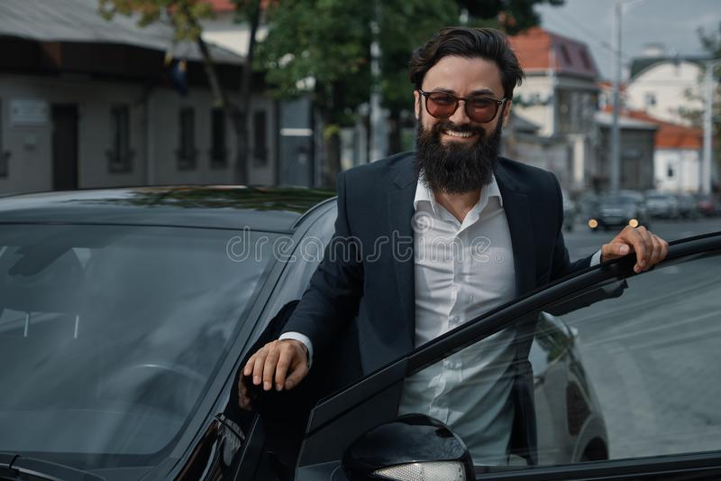 Portret modieuze, knappe mens dichtbij auto in openlucht royalty-vrije stock afbeelding