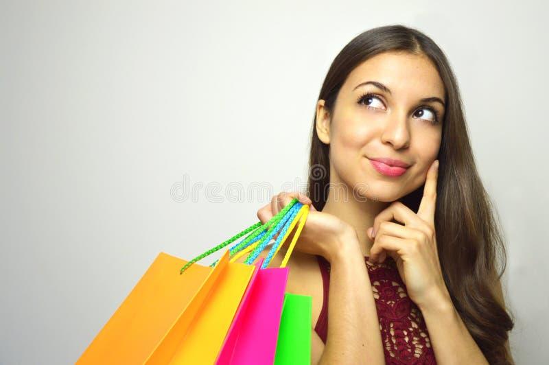 Portret modna wspaniała brunetka z torba kupującym w jej ręki główkowaniu co kupować i patrzeć strona kopii sp fotografia stock