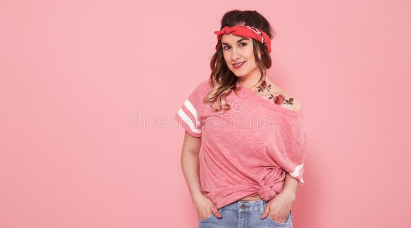 Portret modniś dziewczyna z tatuażem, odosobniony na różowym tle obrazy stock