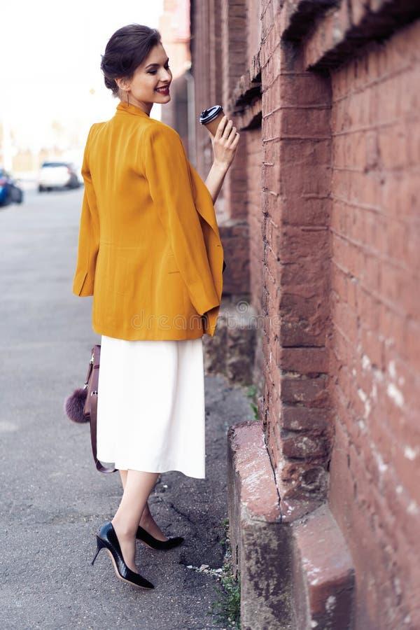 Portret mody kobiety odprowadzenie na ulicie Jest ubranym żółtą kurtkę, ono uśmiecha się popierać kogoś obraz stock