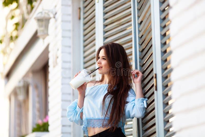 Portret mooi meisje met lang haar in het toevallige uitrusting stellen bij de Italiaanse koffie Het mooie brunette houdt koffie royalty-vrije stock foto
