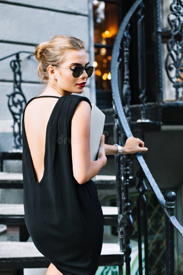 Portret mooi model in zwarte korte kleding met naakt terug op treden openlucht Zij draagt laptop ter beschikking, zonnebril royalty-vrije stock foto