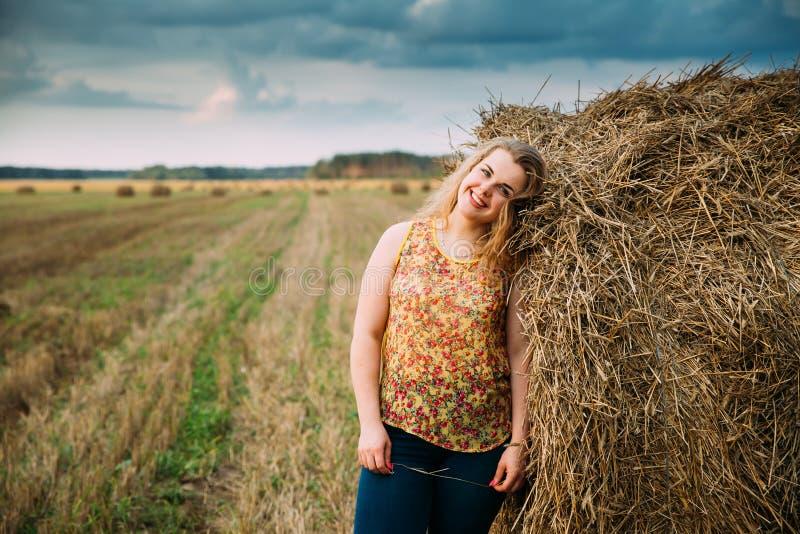 Portret Mooi plus Grootte Jonge Vrouw Status dichtbij Hay Bale royalty-vrije stock foto's