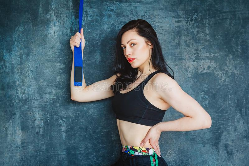Portret mooie atletische vrouw met blauwe riem Vechtsportenconcept Binnen, studioschot Reeks op een grijze achtergrond stock afbeeldingen