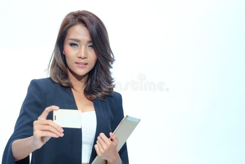 Portret mooie Aziatische vrouw status, Greeptablet en nameca stock afbeelding