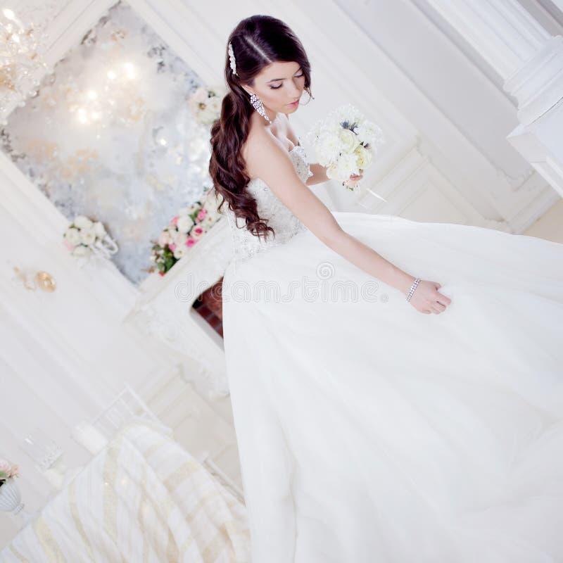 Portret mooie bruid met een boeket van bloemen De decoratie van het huwelijk Aanbiddelijk meisje die haar rok houden stock afbeelding