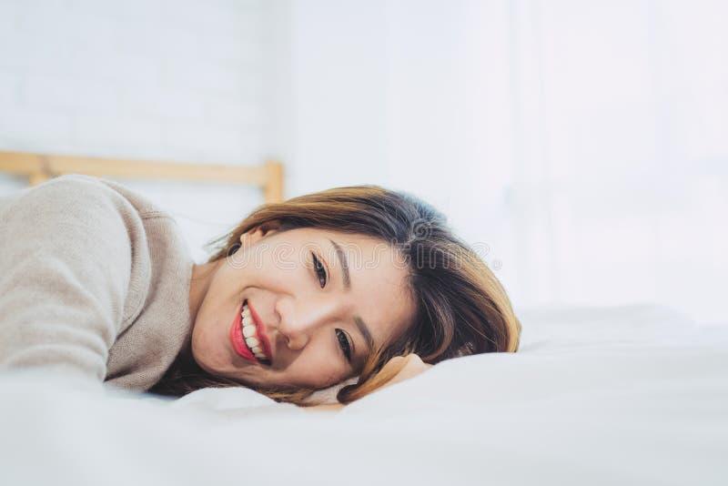 Portret mooie jonge Aziatische vrouw op bed thuis in de ochtend stock afbeelding