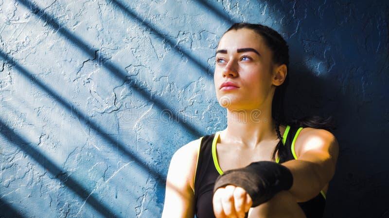 Portret mooie jonge in dozen doende vrouw die na opleiding na ponsen in gymnastiek rusten royalty-vrije stock afbeelding