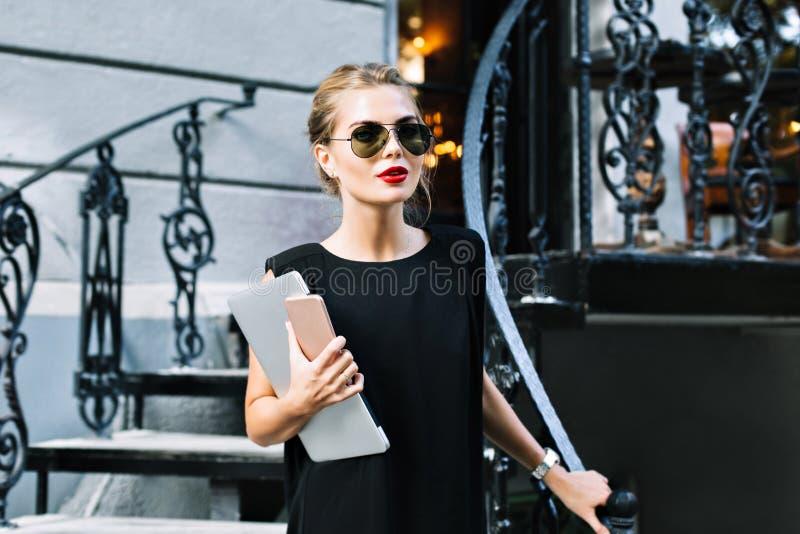 Portret mooie onderneemster in zwarte kleding op treden openlucht Zij draagt zonnebril, laptop, telefoon, die aan camera kijken stock foto's