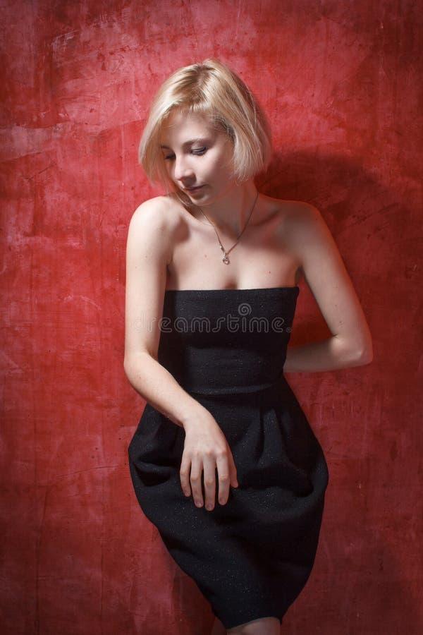 Portret mooie vrouw in kleding op grungemuur stock fotografie