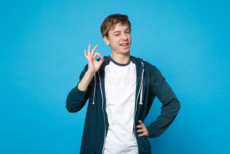 Portret mrugać śmiesznego młodego człowieka stoi OK gest odizolowywającego na błękit ściany tle i pokazuje w przypadkowych ubrani obrazy royalty free