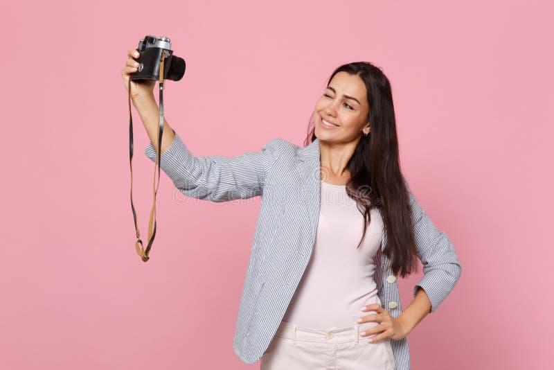 Portret mruganie młoda kobieta w pasiastej kurtce robi selfie strzałowi na retro rocznik fotografii kamerze odizolowywającej na m zdjęcia royalty free