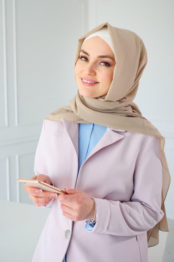 Portret muzułmańska biznesowa kobieta w beżowym hijab z telefonem komórkowym w biurze zdjęcie stock