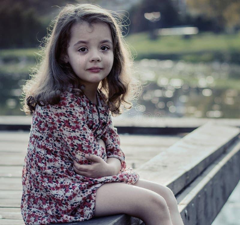 Portret nędzny małej dziewczynki obsiadanie na jetty obrazy stock